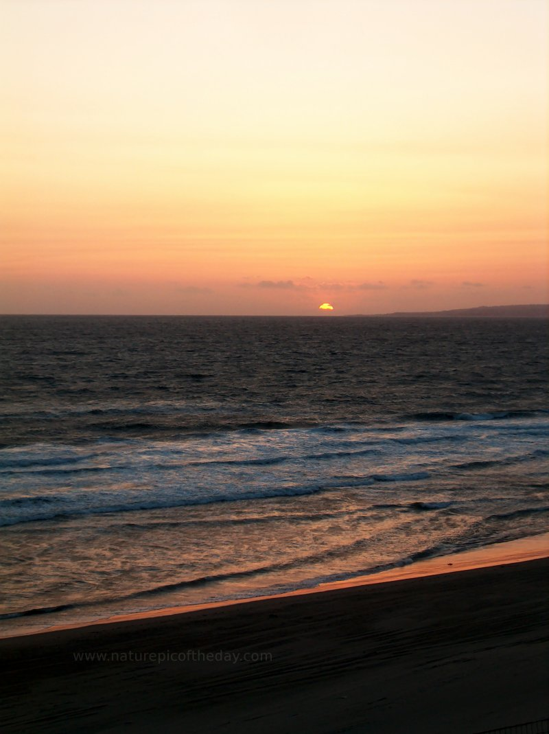 Picture of sun setting over the Pacific Ocean from a beach.