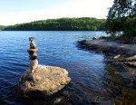 Stack of rocks next to a lake.