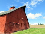 A red barn on a green lawn under a blue sky in Idaho.